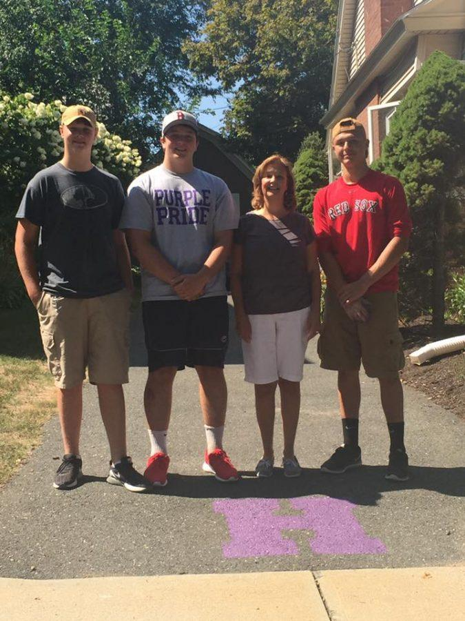 Members of the football team and HHS teacher Jill Reardon show off the new purple H.