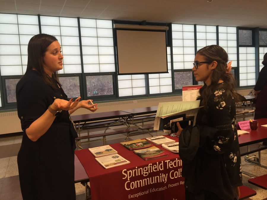 An admissions representative from Springfield Technical Community College discussing their school with a Holyoke High student.